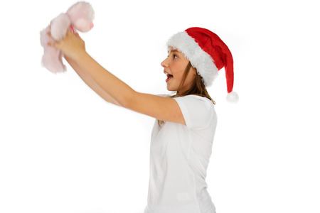 edu: Excited young girl in a Santa Hat holding up a pink toy teddy bear that she has just received as a Christmas gift, on white Stock Photo
