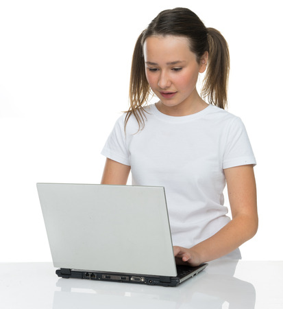 12 13: Pretty young girl with her brown hair in pigtails sitting at a table using a laptop computer, on white