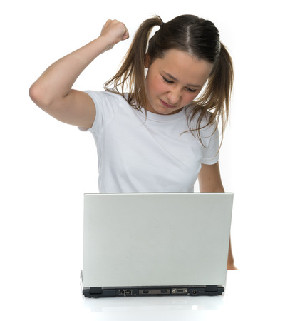 12 13: Angry young girl attacking her laptop computer raising her fist in frustration, isolated on white