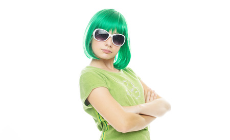 glaring: Girl with an attitude in an iridescent green wig and sunglasses standing glaring at the camera with folded arms, on white with copyspace