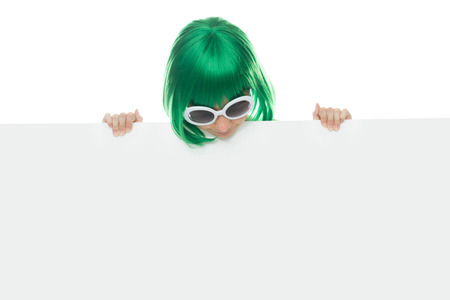 edu: Cute young girl in a green wig and stylish sunglasses holding a blank white sign with copyspace for your text or advertising Stock Photo