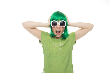 edu: Fun young girl in a green wig and trendy white sunglasses holding her hands to her head with a look of shocked amazement