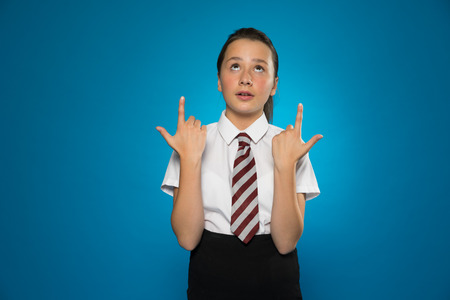 edu: Attractive schoolgirl pointing above her head with both hands while looking up in the same direction, on blue Stock Photo