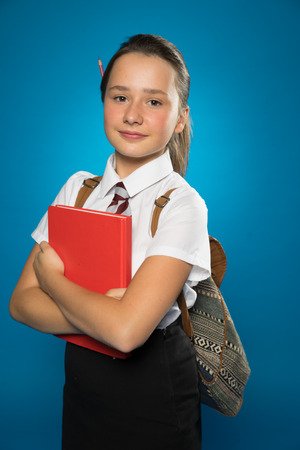 edu: Pretty tanned young schoolgirl with a text book clutched in her arms standing in her school uniform and backpack looking at the camera with a smile Stock Photo