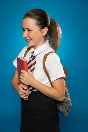 shool: Happy young schoolgirl in her school uniform carrying a tex book with her backpack over her shoulders, side view on blue