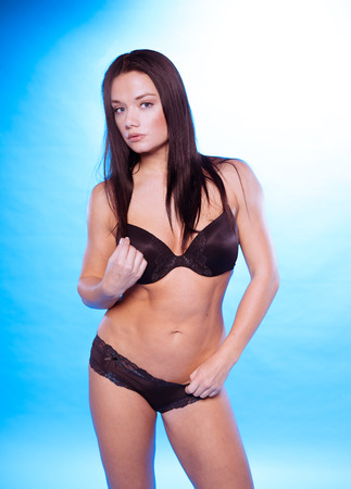 silky lingerie: Sexy Young Woman in Black Underwear, Bra and Panty, Looking at Camera. Isolated on Gradient Sky Blue. Stock Photo