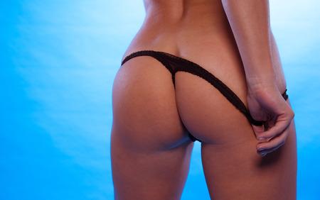 culo: Cierre para arriba Mujer Sexy culo con la ropa interior Negro T-back, aislado en el degradado del cielo azul de fondo