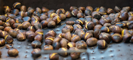 healthy snack: Background texture of fresh roasted chestnuts cooling on a metal tray ready to be eaten as a healthy snack or dessert