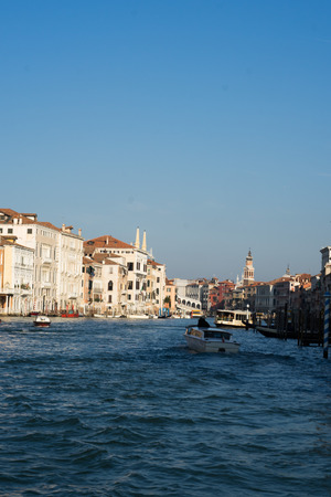 waterbus: View down the Grand Canal, Venice looking towards the Rialto Bridge partially visible on the bend with a vaparetto waterbus and boats on the waterway