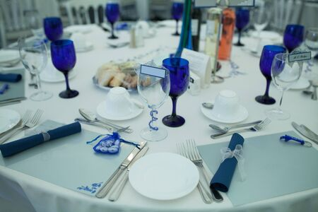 party favors: Elegant formal table setting at a wedding reception with white linen and dinnerware with royal blue accents, name place markers and party favors, closeup view Stock Photo