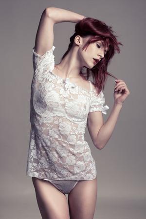 jungen unterwäsche: Vorderansicht der sinnlichen jungen Frau in der beiläufigen weißen Hemd und Höschen, posiert mit den Händen auf Haar. Auf grauem Hintergrund isoliert.