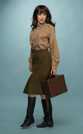 suit case: Full Length of Fashionable Young Woman In Trendy Clothing and Black Boots Carrying Suit Case on Light Blue Green Background.