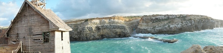 steep cliffs: Old derelict wooden house overlooking the sea and a rocky inlet with steep cliffs and turquoise blue water