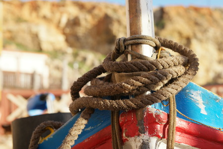 stanchion: Close up Old Brown Rope Tie on a Vintage Boat at the Dock. Stock Photo