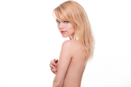 half nude: Portrait of Young Blond Woman Posing Nude in Studio Covering Breasts with Hands Looking Over Shoulder at Camera on White Background