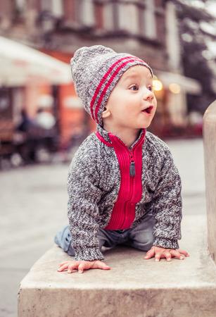 babies hands: happy little baby boy wearing hat in the city