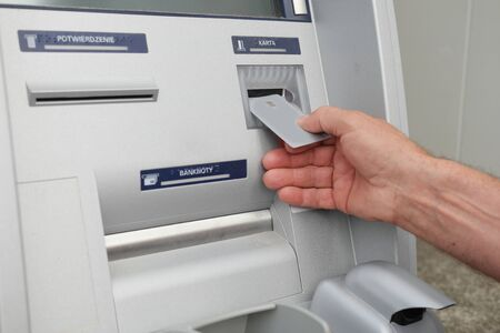 Close up of hand of a man using banking machine photo