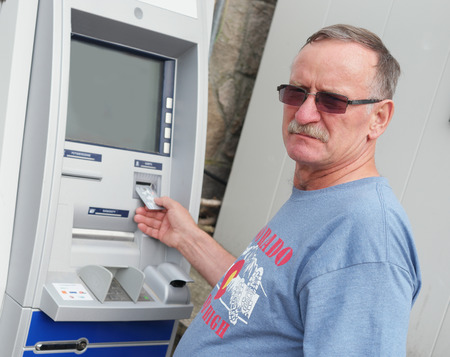 withdrawing: man withdrawing money from ATM machine