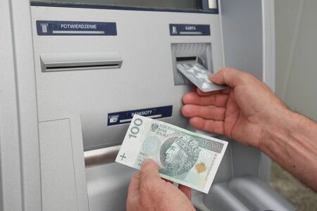 automatic teller machine bank: Close up of hand of a man using banking machine in Poland taking sto zlotych Stock Photo