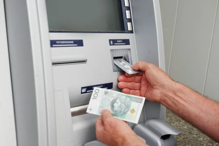 Close up of hand of a man using banking machine in Poland taking sto zlotych photo