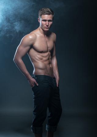 hombre sin camisa: Retrato de un modelo masculino muscular contra el fondo oscuro con humo.