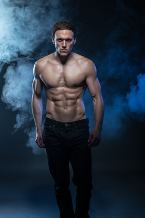 cat walk: Portrait of a muscular male model against dark background with smoke. cat walk