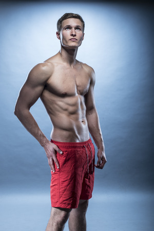 shorts: blonde Male fitness model wearing red shorts on blue