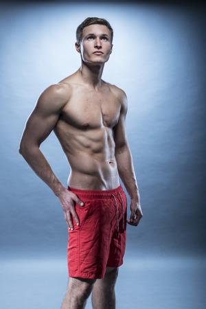 pantalones cortos: rubia modelo de fitness masculino con pantalones cortos de color rojo en azul