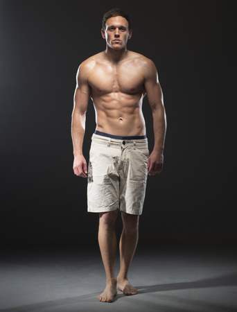 shirtless male: fitness male model cat walk on black