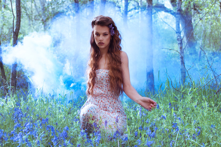 catchy: Artistic portrait of a pretty young redhead girl in a bluebell forest kneeling amongst the flowers with an applied blue filter for ambiance and atmosphere Stock Photo