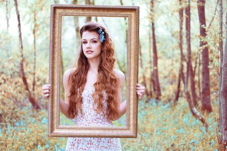 ravishing: Ravishing beautiful redhead long haired woman wearing a low-cut sleeveless dress with floral pattern while looking at camera through a brown handheld portrait frame in a deciduous forest