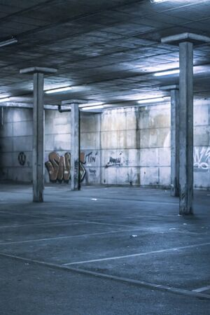 subterranean: Interior of an undercover parking area with empty parking bays and a concrete construction with pillars