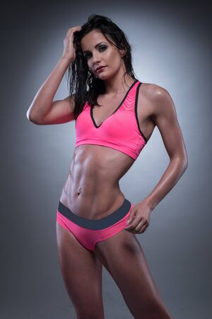 athletic wear: Portrait of a Sensual Athletic Woman Posing in Pink with Gray Sexy Fitness Wear, on a Gray Gradient Background. Stock Photo