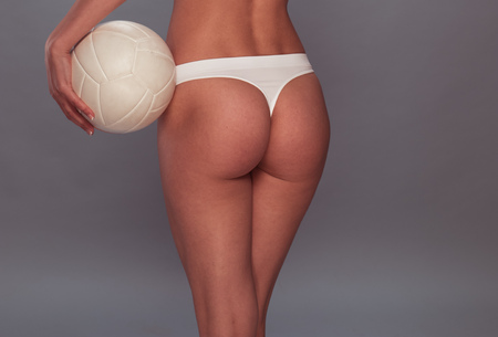 thong panties: Close up Rear View of a Sexy Body of a Woman, Wearing White Thong, Holding a Volleyball Ball on a Gray Background.