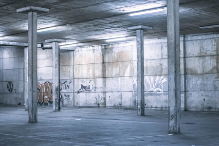 car park: Interior of an undercover parking area with empty parking bays and a concrete construction with pillars