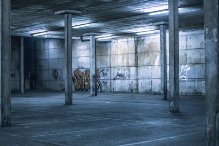 undercover: Interior of an undercover parking area with empty parking bays and a concrete construction with pillars