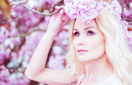 Beauty in springtime with a full length portrait of a gorgeous young blond woman in a long white dress standing in front of pink spring blossom looking down with a gentle serious expression