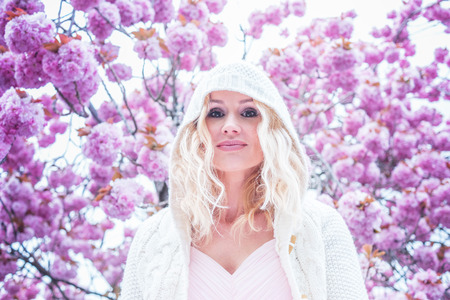 faraway: Gorgeous dreamy young woman with long blond hair standing in spring blossom looking up into the air with a faraway expression, close up view of her face Stock Photo