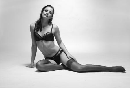 mujeres sentadas: Retrato de una mujer muy sensual, el uso de la ropa interior atractiva, sentado en el suelo y mirando a la cámara en color blanco y negro. Foto de archivo