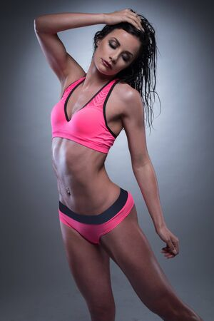 desirable: Portrait of a Sensual Athletic Woman Posing in Pink with Gray Sexy Fitness Wear, on a Gray Gradient Background. Stock Photo