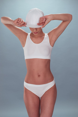gstring: Portrait of a Sexy Young Woman, Wearing White Undies, Holding her Cap While Looking Down. Isolated on Gray.
