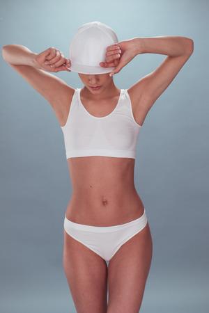 Portret van een sexy jonge vrouw, die Witte Ondergoed, Holding haar Cap bij het zoeken Down. Geïsoleerd op grijs.