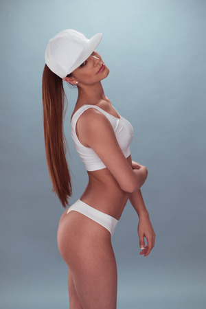gstring: Portrait of a Sexy Long-Haired Woman, Wearing White Underwear with Cap, Crossing her Arm Over her Stomach While Looking at the Camera. Isolated on a Gray Background. Captured in Side View. Stock Photo