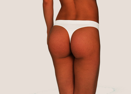gstring: Close up Sexy Young Woman Wearing White G-String Underwear on an Off White Background, Captured in Rear View