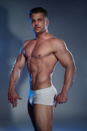 female muscle: Muscular Man in White Boxer Shorts on grey background
