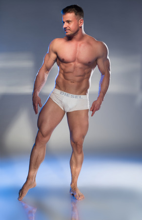 Muscular Man in White Boxer Shorts on grey background