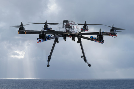 policing: Close up view of a hexacopter drone in midair flying over the ocean against a backdrop of stormy grey clouds and a rain squall Stock Photo