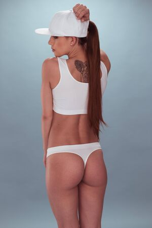 gstring: Rear View Portrait of a Young Woman with Long Hair, Wearing White Underwear and Cap, Looking to the Left of the Frame. Isolated on Gray Background.