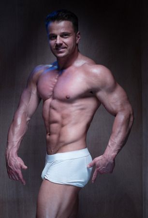 boxer shorts: Muscular Man Wearing Tight White Boxer Shorts Looking Down and To the Side in Dimly Lit Room