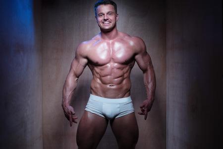 musculoso: Hombre muscular Wearing Tight Boxer Blanco Shorts Mirar hacia abajo y hacia el lado en poco iluminada habitación Foto de archivo